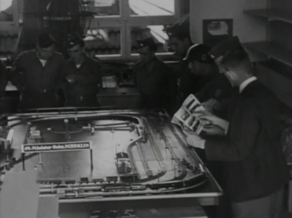 U.S. Soldiers observe layout in the Märklin factory showroom and browse a pre-war catalog with a Märklin salesman.